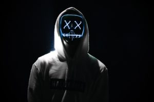 A figure with lit up X's for eyes wears a white hoodie against a black background.