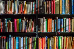 Three rows of a black book shelf full of books in a rainbow of colours.