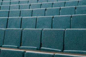 Rows of blue lecture hall chairs.